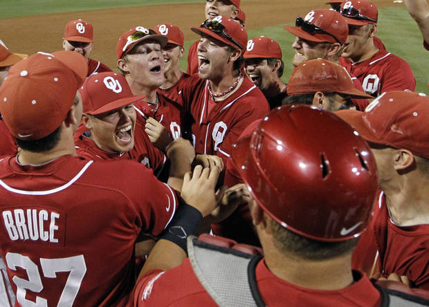 UNIVERSITY OF OKLAHOMA / OU / NCAA TOURNAMENT / NCAA BASEBALL TOURNAMENT: Oklahoma players and coaches celebrate their 5-2 victory over Appalachian State in an NCAA college baseball tournament regional game, Monday, June 4, 2012 at Davenport Field in Charlottesville, Va. (AP Photo/Andrew Shurtleff) ORG XMIT: VAAS119
