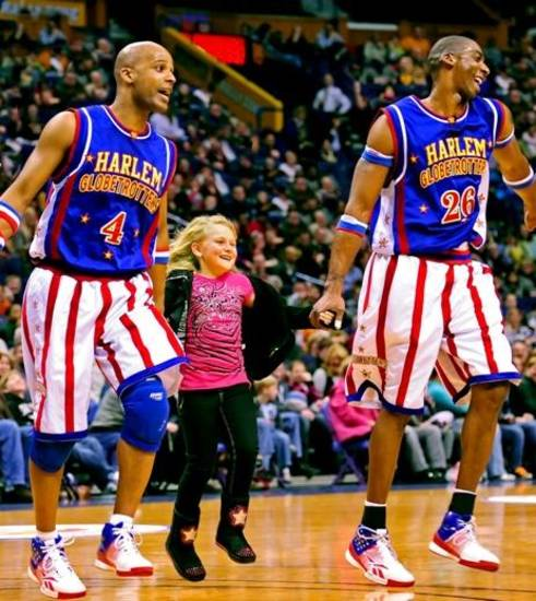 Flight Time and Hi-Lite of the Harlem Globetrotters entertain a girl at a recent tour stop for the basketball stunt squad.