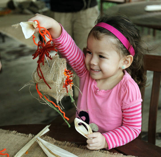 Malaya Ariete, 3, creates a wreath during Pumpkinville at Myriad Botanical Gardens in Oklahoma City. Photos by Paul Hellstern, The Oklahoman