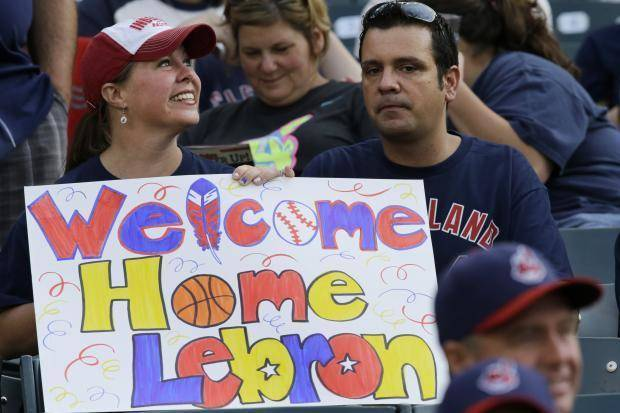 Cleveland fans hold a sign welcoming home LeBron James to Cleveland. (AP photo)