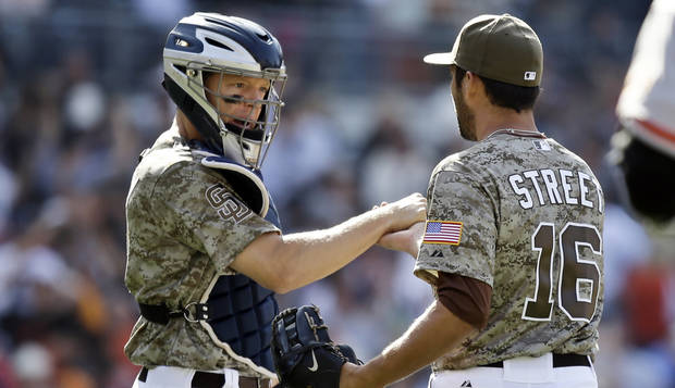 San Diego Padres catcher Nick Hundley congratulates closer Huston Street after Street saved the Padres' 6-4 win over the San Francisco Giants in a baseball game in San Diego, Sunday, April 28, 2013. (AP Photo/Lenny Ignelzi)