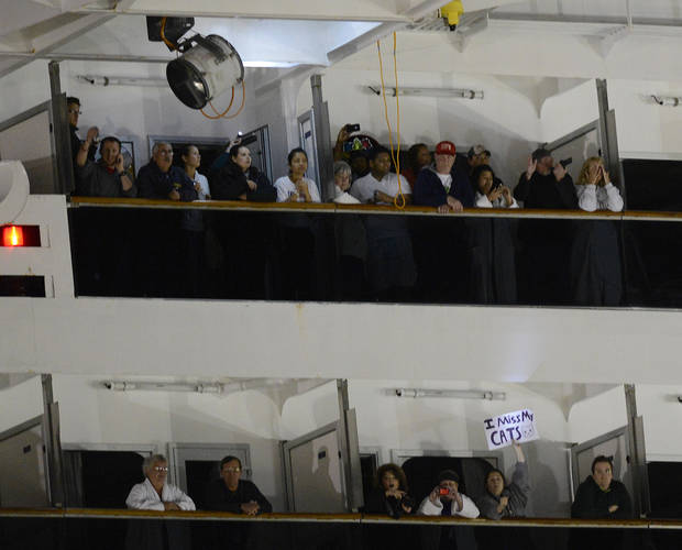 People watch from their balconies and hold up signs aboard the Carnival Triumph after it was towed to the cruise terminal in Mobile, Ala., Thursday, Feb. 14, 2013. The ship with more than 4,200 passengers and crew members has been idled for nearly a week in the Gulf of Mexico following an engine room fire. (AP Photo/John David Mercer)