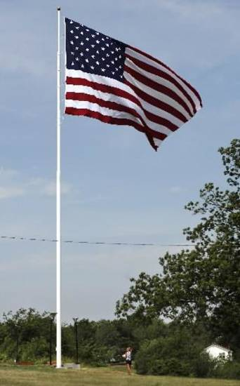 Citizens of Drumright celebrated Flag Day by raising a huge American flag 100 feet into the air above Cleo Hutchison Centennial Memorial Park Thursday morning, June 14, 2012. Photo by Jim Beckel