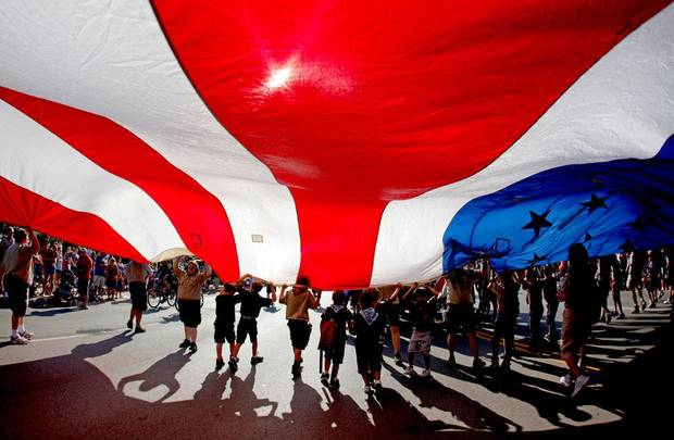 Boy Scouts and others carry a large American flag during the LibertyFest Fourth of July Parade in Edmond, Okla., Wednesday, July 4, 2012. Photo by Bryan Terry, The Oklahoman