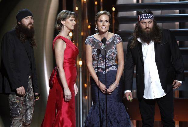 """Duck Dynasty"" cast members, from left, Jase Robertson, Missy Robertson Korie Robertson and Willie Robertson speak onstage at the 47th annual CMA Awards at Bridgestone Arena on Wednesday, Nov. 6, 2013, in Nashville, Tenn. (AP)"