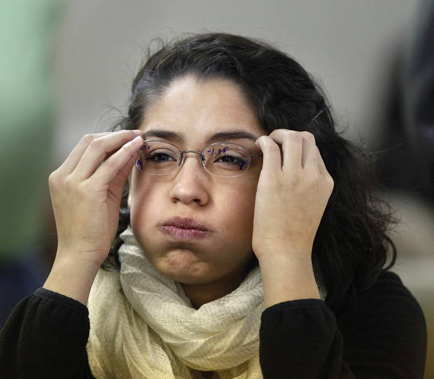 Ilse Zapata, 18, squints to read the eye chart as she tries on a  pair of glasses. Zapata, a senior at U.S. Grant High School in Oklahoma City, received her first pair of glasses at the free eye clinic. Photo by Jim Beckel, The Oklahoman <strong>Jim Beckel - THE OKLAHOMAN</strong>