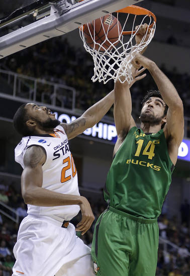 Oregon forward Arsalan Kazemi (14) dunks over Oklahoma State forward Michael Cobbins (20) during the first half of a second-round game in the NCAA college basketball tournament in San Jose, Calif., Thursday, March 21, 2013. (AP Photo/Ben Margot) ORG XMIT: SJA126