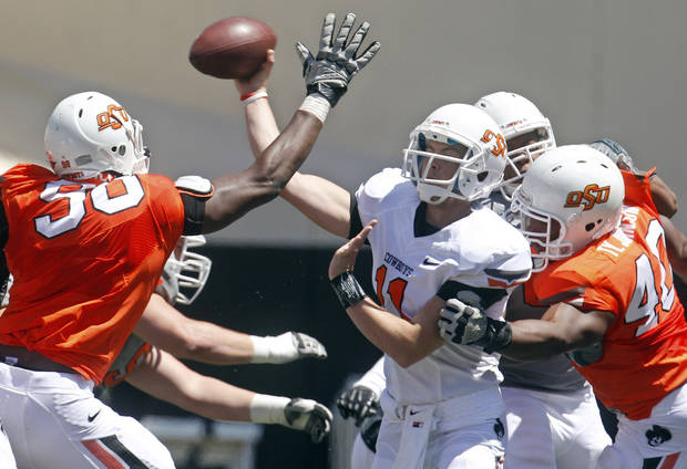 Oklahoma State quarterback Wes Lunt, center, throw under pressure from defenders Davidell Collins (98) and Tyler Johnson (40) during a spring NCAA college football game in Stillwater, Okla., Saturday, April 21, 2012. (AP Photo/Sue Ogrocki)