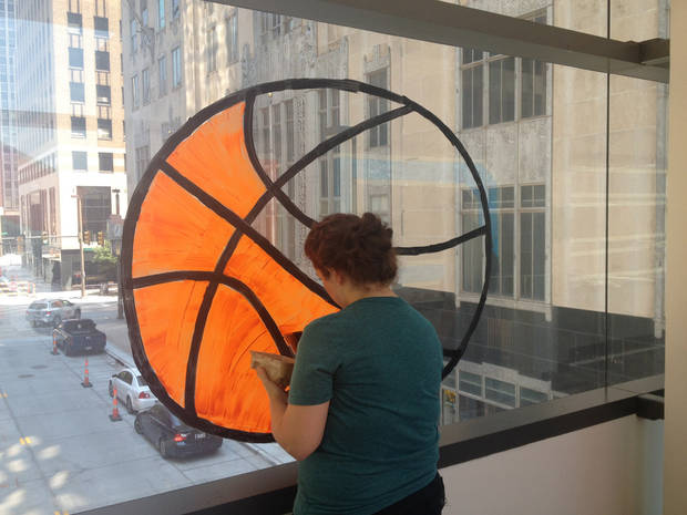 Jill Delozier, Marketing Director at Downtown OKC, Inc. tests her basketball (painting) skills. We give her an A+.