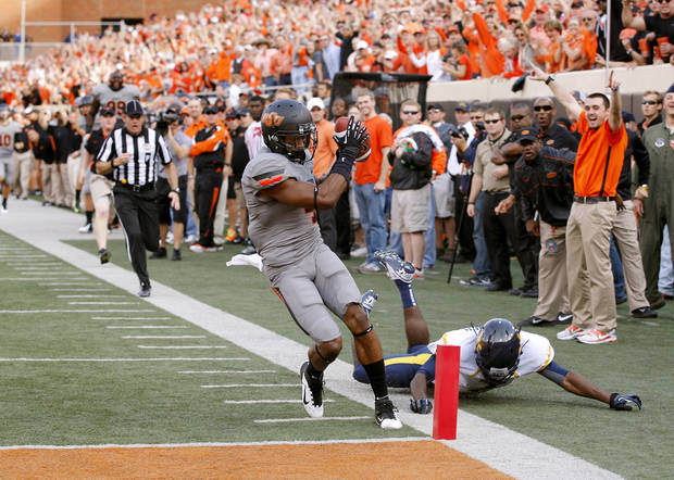 Oklahoma State's Justin Gilbert (4) scores a touchdown past West Virginia's Nana Kyeremeh (7) on a kickoff return during a college football game between Oklahoma State University (OSU) and the University of West Virginia at Boone Pickens Stadium in Stillwater, Okla., Saturday, Nov. 10, 2012. Photo by Bryan Terry, The Oklahoman