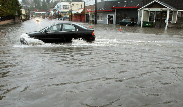 A car attempts to navigate through the deep water on Bay Street in Port Orchard, Wash., on Monday. Nov. 19, 2012. Heavy rains inundated the areas storm drains and caused flooding in the Port Orchard, Wash., downtown district and elsewhere in Kitsap County. (AP Photo/Kitsap Sun, Meegan M. Reid)