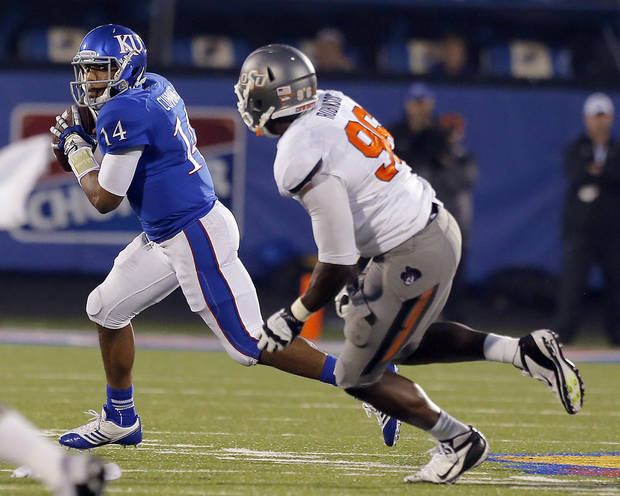 Kansas' Michael Cummings (14) looks to pass as Oklahoma State's Calvin Barnett (99) defends during the fourth quarter of the college football game between Oklahoma State University (OSU) and the University of Kansas (KU) at Memorial Stadium in Lawrence, Kan., Saturday, Oct. 13, 2012. Photo by Sarah Phipps, The Oklahoman