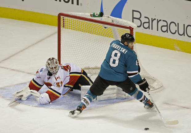 San Jose Sharks center Joe Pavelski, right, looks for the puck after his shot was blocked by Calgary Flames goalie Karri Ramo, left, during the first period of an NHL hockey game Saturday, Oct. 19, 2013, in San Jose, Calif. (AP Photo/Eric Risberg)