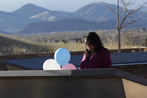 CORRECTS YEAR PHOTO WAS TAKEN - A former student at Columbine High School, who preferred her name not be used, reads a plaque at the Columbine Memorial, where someone had left balloons and a note for the victims of last week's deadly shootings at a Connecticut elementary school, in Littleton, Colo., Monday Dec. 17, 2012. Columbine and other sites of mass shootings have been rebuilt by residents determined to reclaim public places invaded by gunmen. Deciding what to do with the scene of a tragic event often determines how a community will heal. (AP Photo/Brennan Linsley) ORG XMIT: COBL101