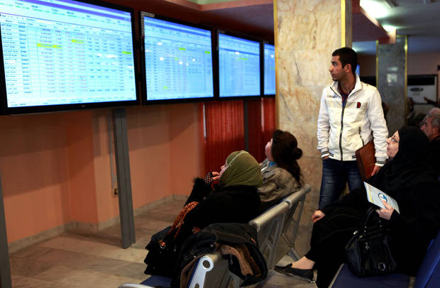 Iraqi stock traders watch the sales screen at the Iraq Stock Exchange in Baghdad, Iraq, Sunday, Feb. 3, 2013. The Iraqi mobile phone company Asiacell sold a 25 percent stake to investors Sunday, raising more than $1.3 billion in one of the region's largest share offers in years. The floatation on the low-volume Iraq Stock Exchange was seen as a test of investor confidence. (AP Photo/Hadi Mizban)