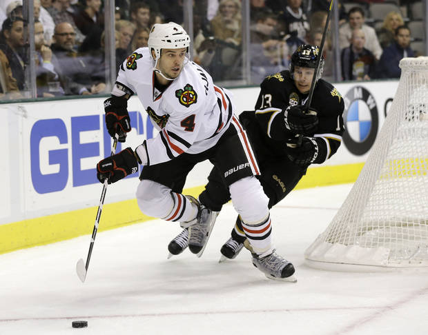 Chicago Blackhawks defenseman Niklas Hjalmarsson (4), of Sweden, prepares to pass from behind the net as Dallas Stars' Ray Whitney (13) pressures in the first period of an NHL hockey game on Thursday, Jan. 24, 2013, in Dallas. (AP Photo/Tony Gutierrez)