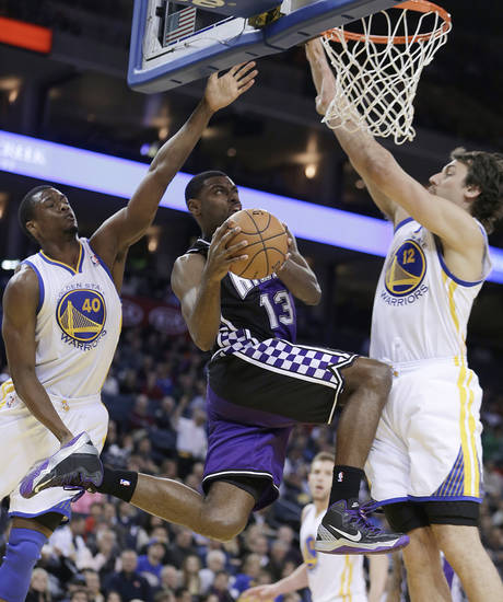 Sacramento Kings' Tyreke Evans (13) goes up for a shot between Golden State Warriors' Harrison Barnes, left, and Andrew Bogut (12) during the first half of an NBA basketball game Wednesday, March. 6, 2013, in Oakland, Calif. (AP Photo/Ben Margot)