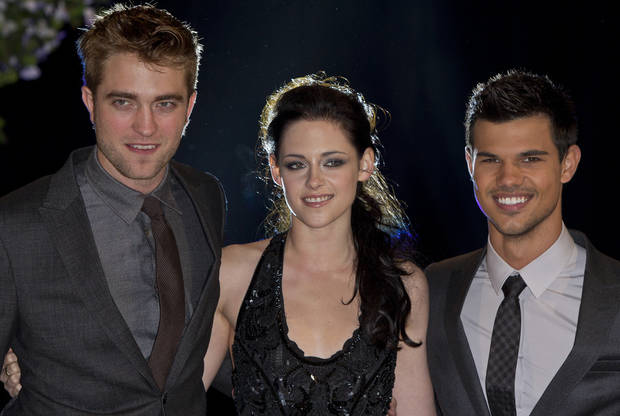 British actor Robert Pattinson, left, US actress Kristen Stewart, centre, and US actor Taylor Lautner arrive for the UK film premiere of 'Twilight Breaking Dawn Part 1' at Westfield Stratford in east London, Wednesday, Nov. 16, 2011. (AP Photo/Joel Ryan) ORG XMIT: LENT104
