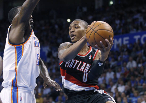 Portland Trail Blazers guard Damian Lillard (0) drives under the basket in front of Oklahoma City Thunder center Kendrick Perkins during the first quarter of an NBA basketball game in Oklahoma City, Friday, Nov. 2, 2012. Oklahoma City won 106-92. (AP Photo/Sue Ogrocki) ORG XMIT: OKSO121