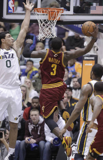 Cleveland Cavaliers' Dion Waiters (3) goes the the basket as Utah Jazz's Enes Kanter (0) defends in the second half during an NBA basketball game Saturday, Jan. 19, 2013, in Salt Lake City. The Jazz defeated the Cavaliers 109-98. (AP Photo/Rick Bowmer)