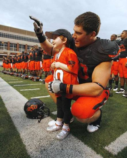Taylor Brandt, 5, joins Oklahoma State�s Cooper Bassett in celebration and singing the school song after the Cowboys� 70-28 win over Kansas on Oct. 8. Photo by Steve Sisney, The Oklahoman