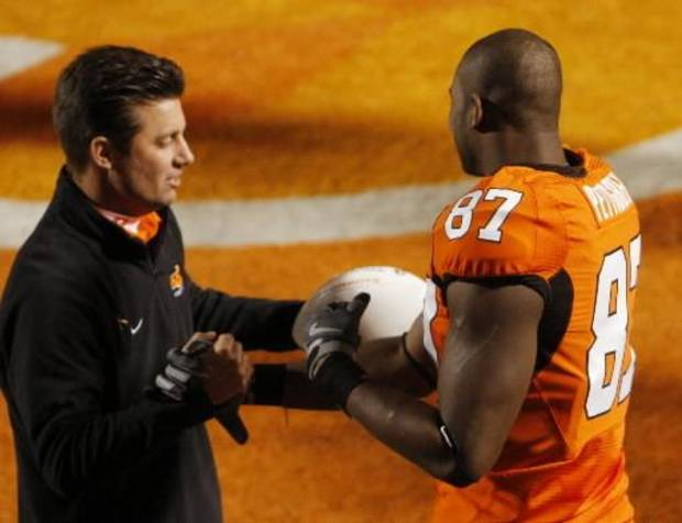 Mike  Gundy gives Brandon Pettigrew a game ball on senior day during the first half of the college football game between the University of Oklahoma Sooners (OU) and Oklahoma State University Cowboys (OSU) at Boone Pickens Stadium on Saturday, Nov. 29, 2008, in Stillwater, Okla. STAFF PHOTO BY DOUG HOKE