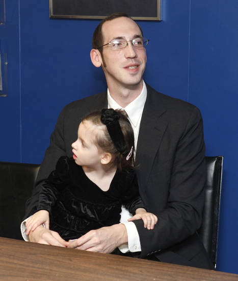 Daniel Becannan, who informed police about a murder-for-hire solicitation, sits with his two-year-old daughter Angela before receiving an award from Edmond Police Chief Bob Ricks at the Edmond Police Station in Edmond, OK, Friday, Jan. 27, 2012. By Paul Hellstern, The Oklahoman