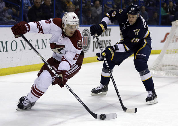 Phoenix Coyotes' Antoine Vermette, left, controls the puck as St. Louis Blues' Jay Bouwmeester defends during the first period of an NHL hockey game on Thursday, April 18, 2013, in St. Louis. (AP Photo/Jeff Roberson)