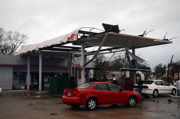 Hattiesburg Police officers talk to onlookers at a damaged gas station in Hattiesburg, Miss. after an apparent tornado that moved through area on Sunday, Feb. 10, 2013. (AP Photo/The Hattiesburg American, Bryant Hawkins) ORG XMIT: MSHAT110