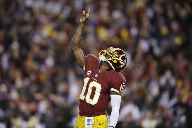 Washington Redskins quarterback Robert Griffin III celebrates a touchdown during the first half of an NFL football game against the Dallas Cowboys on Sunday, Dec. 30, 2012, in Landover, Md. (AP Photo/Evan Vucci) ORG XMIT: FDX113