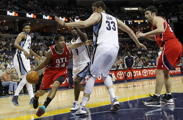 Atlanta Hawks guard Devin Harris (34) drives to the basket against Memphis Grizzlies defenders Rudy Gay (22), Tony Allen (9) and Marc Gasol (33) with Hawks teammate Zaza Pachulia, right, in the first half of an NBA basketball game on Saturday, Dec. 8, 2012, in Memphis, Tenn. (AP Photo/Lance Murphey)