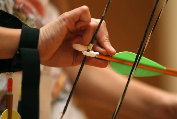 A student places an arrow on a bow during an archery class designed to teach the proper fundamental shooting form. PHOTO BY BRYAN TERRY, THE OKLAHOMAN. <strong>BRYAN TERRY - THE OKLAHOMAN</strong>