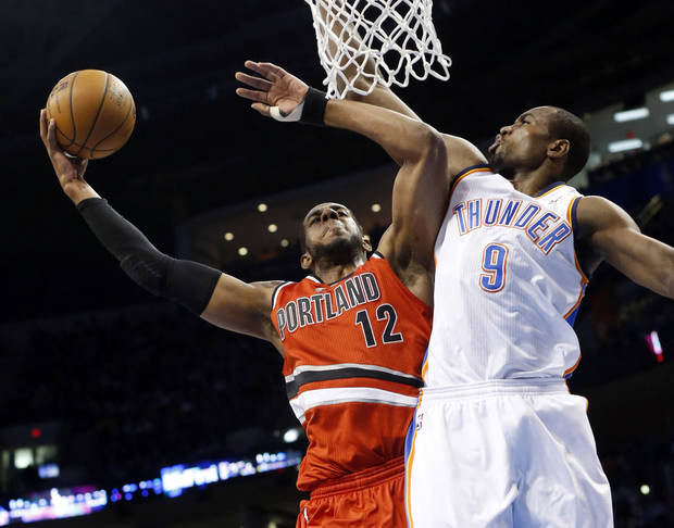 Portland Trail Blazers forward LaMarcus Aldridge (12) is fouled by Oklahoma City Thunder forward Serge Ibaka (9) during the first quarter of an NBA basketball game in Oklahoma City, Sunday, March 24, 2013. (AP Photo/Sue Ogrocki) ORG XMIT: OKSO103
