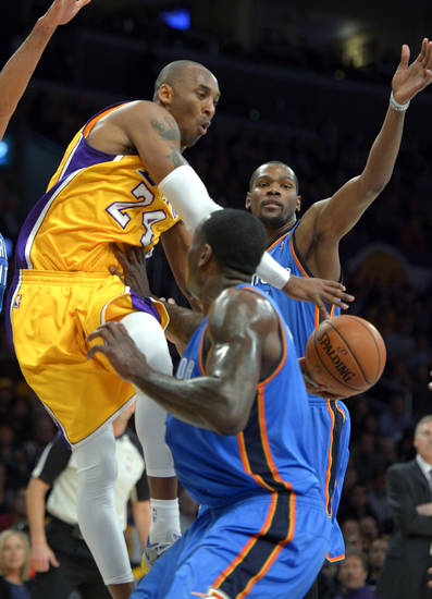 Los Angeles Lakers guard Kobe Bryant, left, passes between Oklahoma City Thunder forward Kevin Durant, back, and center Kendrick Perkins during the first half of their NBA basketball game, Friday, Jan. 11, 2013, in Los Angeles. (AP Photo/Mark J. Terrill)