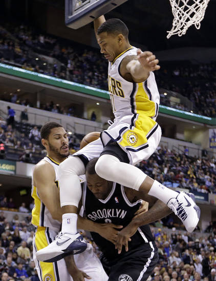 Indiana Pacers guard Orlando Johnson, top, comes down on the head of Brooklyn Nets forward Andray Blatche, bottom right, as Blatche was fouled by Pacers forward Jeff Pendergraph in the first half of an NBA basketball game in Indianapolis, Monday, Feb. 11, 2013.  (AP Photo/Michael Conroy)
