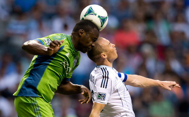 Seattle Sounders' Jhon Kennedy Hurtado, left, heads the ball above Vancouver Whitecaps' Kenny Miller, of Scotland, during the first half  of an MLS soccer  match in Vancouver, British Columbia, on Saturday, July 6, 2013. (AP Photo/The Canadian Press, Darryl Dyck)