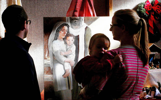 Randy Hempel and his wife, Tara, who holds their one-year-old daughter, Mya, look at an image of Mary,  Joseph and the infant Jesus in this painting of the Nativity scene at the Church of Jesus Christ of Latter-day Saints. Photos by Jim Beckel, The Oklahoman