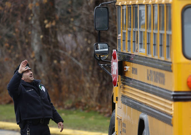 Easton police officer J. Sollazzo waves to returning children as their bus pulls into Hawley School, Tuesday, Dec. 18, 2012, in Newtown, Conn.  Classes resume Tuesday for Newtown schools except those at Sandy Hook. Buses ferrying students to schools were festooned with large green and white ribbons on the front grills, the colors of Sandy Hook. At Newtown High School, students in sweatshirts and jackets, many wearing headphones, betrayed mixed emotions.  Adam Lanza walked into Sandy Hook Elementary School in Newtown,  Friday and opened fire, killing 26 people, including 20 children, before killing himself.(AP Photo/Jason DeCrow)