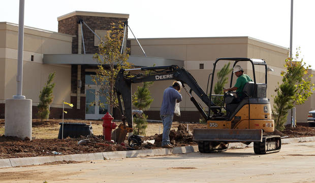 The front landscape at Ronald Reagan Elementary School gets some last-minute additions as crews ready the school for its first day of classes on Wednesday. PHOTO BY STEVE SISNEY, THE OKLAHOMAN