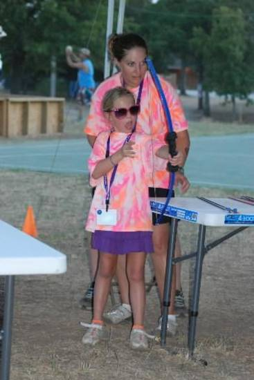 A Crosspointe Church volunteer gives a camper an archery lesson at the church's Royal Family Kids' Camp for children in foster care. Photo provided, August 2011.