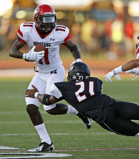 Mustang's Travis Mitchell runs past  Yukon's Matt Cammons during a high school football game in Yukon, Okla., Friday, August 31, 2012. Photo by Bryan Terry, The Oklahoman