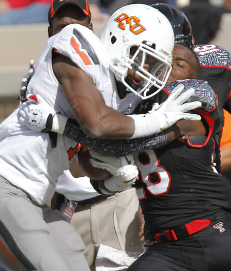 Oklahoma State Cowboys running back Joseph Randle (1) collides with Texas Tech Red Raiders cornerback Happiness Osunde (28) during the college football game between the Oklahoma State University Cowboys (OSU) and Texas Tech University Red Raiders (TTU) at Jones AT&T Stadium on Saturday, Nov. 12, 2011. in Lubbock, Texas.  Photo by Chris Landsberger, The Oklahoman  ORG XMIT: KOD