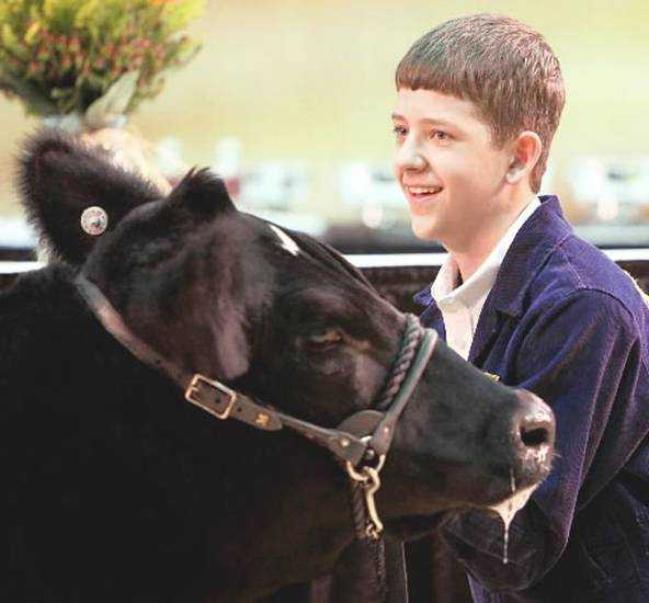 Logan Davis, a member of Newcastle FFA, listens to bids during the auction of his steer.