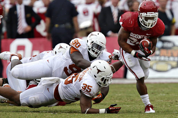 OU&#039;s Brennan Clay (24) runs past UT&#039;s Malcom Brown (90) and Kendall Thompson (35) during the Red River Rivalry college football game between the University of Oklahoma (OU) and the University of Texas (UT) at the Cotton Bowl in Dallas, Saturday, Oct. 13, 2012. Photo by Chris Landsberger, The Oklahoman
