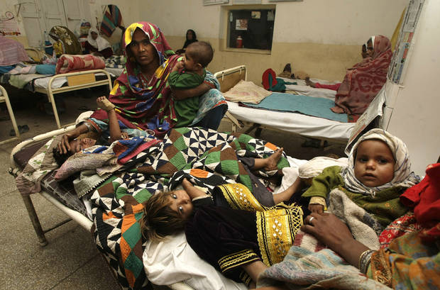 Pakistani family members hold their children suffer from measles, admitted at a local hospital in Sukkar, Pakistan on Tuesday, Jan. 1, 2013.  Measles cases surged in Pakistan in 2012 with hundreds of children dying of the disease, the World Health Organization said Tuesday. Pakistani officials in recent days say they have launched an immunization campaign to reach children in the worst-hit areas. (AP Photo/Fareed Khan)