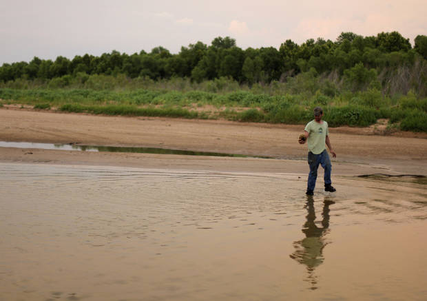 Johnny Heskett picks up a turtle in a rive during a hunting trip near Indianola, Okla., Friday, July 6, 2012.  Photo by Garett Fisbeck, The Oklahoman