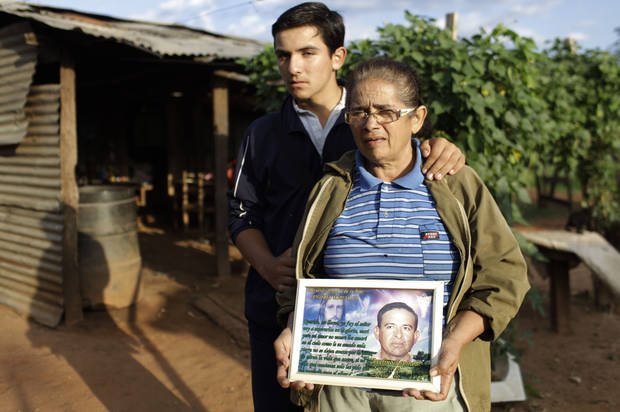In this Nov. 14, 2012 photo, Isabel Iglesias, 56, right, holds a picture of her late husband Avelino Espinola as she poses for a portrait with her son Andres, 14, at their home in the Yvy Pyta settlement near Curuguaty, Paraguay. Iglesias's husband Avelino Espinola was killed during the �Massacre of Curuguaty� on June 15 when negotiations between farmers occupying a rich politician's land ended with a barrage of bullets that killed 11 farmers and 6 police officers. (AP Photo/Jorge Saenz)