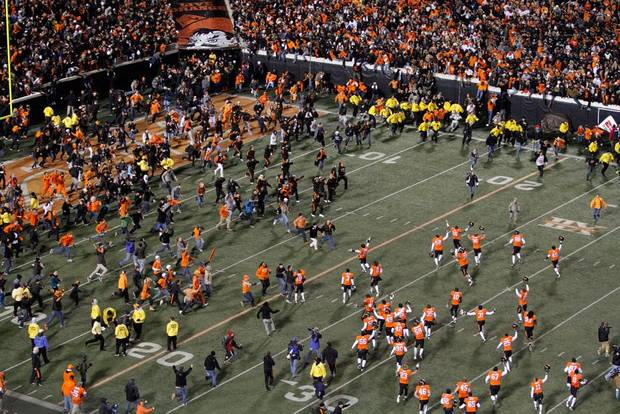 Oklahoma State fans rush the field after the Bedlam college football game between the Oklahoma State University Cowboys and the University of Oklahoma Sooners at Boone Pickens Stadium in Stillwater, Okla., Saturday, Dec. 3, 2011. Photo by Bryan Terry, The Oklahoman