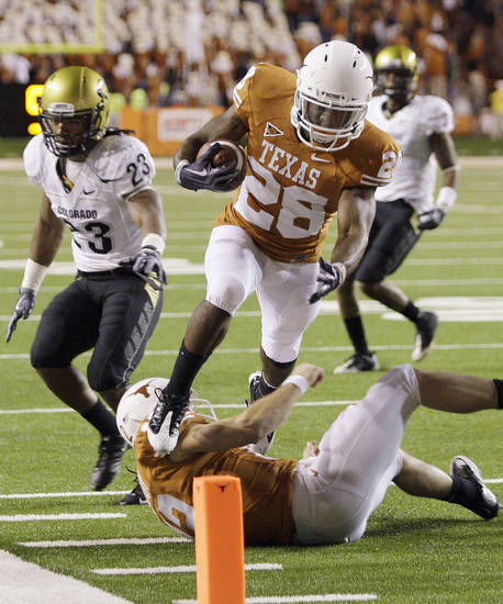 Texas' Fozzy Whittaker (28) leaps over teammate Colt McCoy to score a touchdown against Colorado  during the fourth quarter of their NCAA college football game in Austin, Texas, Saturday, Oct. 10, 2009. Texas won 38-14. (AP Photo/Eric Gay) ORG XMIT: TXUT108
