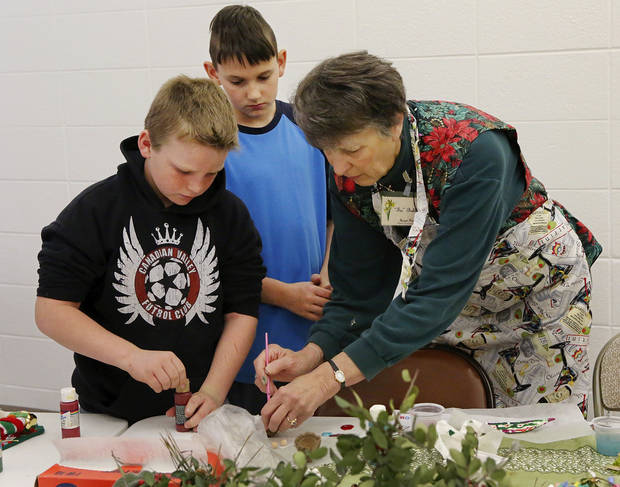 Tis Bohlman, right, helps Briar Mosier, left, and Draper Goostree, both of Mustang, with their ornaments. Bohlman is a member of the Oklahoma City Council of Garden Clubs.